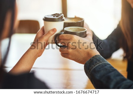 Closeup image of people enjoyed drinking and clinking coffee cups on the table in cafe