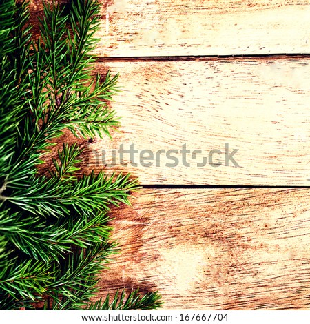 Christmas background with Fir Tree Branch over wood wall. Vintage Christmas Card with copyspace for greeting text. #167667704