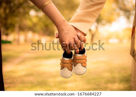 Baby expecting picture with mother and father holding unborn baby shoes, outdoor, garden, parents, family or maternity concept.