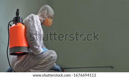 Coronavirus Pandemic. A disinfector in a protective suit and mask sprays disinfectants in the room. Prevention of Coronavirus Disease. Environmental Cleaning and Disinfection with Coronavirus Epidemic #1676694112