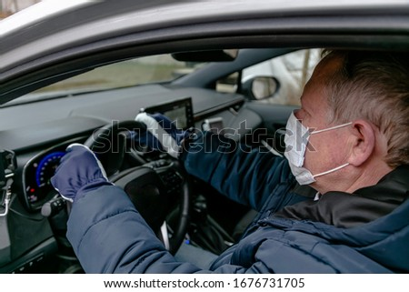 Coronavirus protection. Finnish drivers defend themselves against the virus 03/18/2020 Taxi driver in a protective mask and gloves.  Concept: Stop: Covid-19 #1676731705