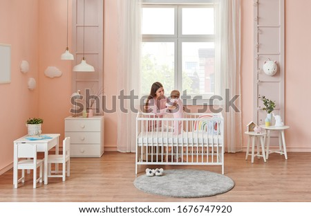 Happy mom is interesting in her baby, in the room, white furniture decor. Cradle and crib style. #1676747920