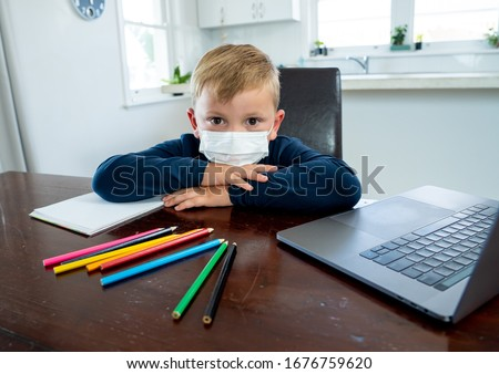Coronavirus Outbreak. Lockdown and school closures. School boy with face mask watching online education classes feeling bored and depressed at home. COVID-19 pandemic forces children online learning. #1676759620