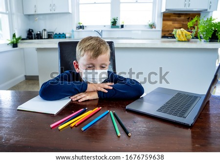 Coronavirus Outbreak. Lockdown and school closures. School boy with face mask watching online education classes feeling bored and depressed at home. COVID-19 pandemic forces children online learning. #1676759638