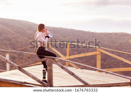 Woman resting after jogging in the nature on wooden bridge with bottle of water in hand #1676765332
