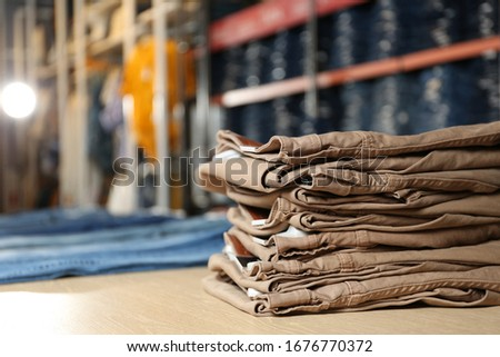 Stack of brown jeans on display in shop #1676770372