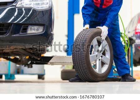 mechanic in uniform is changing a wheels/tires while working in car repair center #1676780107