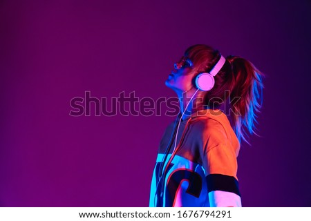 Happy igen teen hipster pretty fashion girl model wear stylish glasses headphones enjoy listen new cool music mix stand at purple studio background in trendy 80s 90s club party light, profile view Royalty-Free Stock Photo #1676794291
