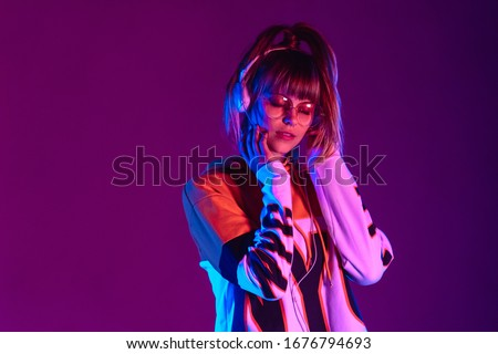 Happy girl wear stylish glasses, headphones listen music at purple background. #1676794693