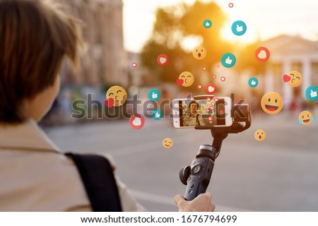 Teen girl blogger vlogger record vlog streaming video hold phone on selfie stick in urban city. Young female vlogger shoot social media blog on smartphone get likes emoji, over shoulder closeup view. #1676794699