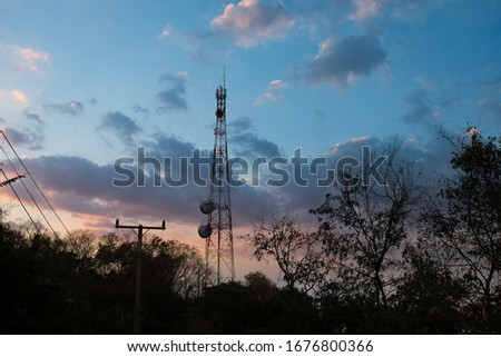 Communication tower with sunset sky background. Mobile phone communication antenna tower with satellite dish. Telecommunication tower. #1676800366