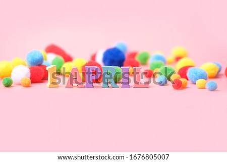 """April Fool's Day. creative minimal festive concept. wooden letters """"1 April"""" and fluffy colorful balls on pink background.  Royalty-Free Stock Photo #1676805007"""