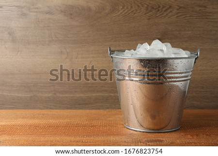 Metal bucket with ice cubes on wooden background. Space for text #1676823754