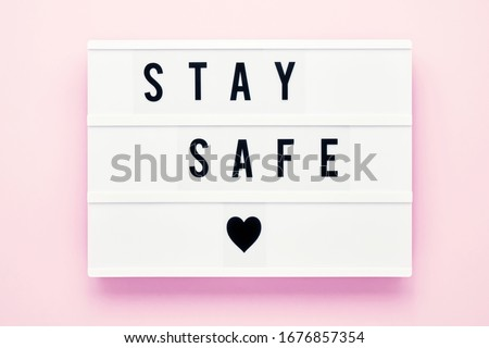 STAY SAFE written in light box on pink background. Healthcare and medical concept. Top view, copy space. Quarantine concept. Royalty-Free Stock Photo #1676857354