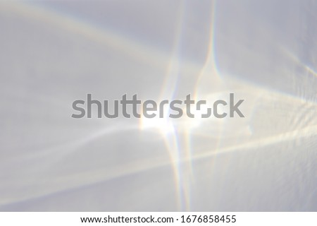 Water texture overlay effect for photo and mockups. Organic drop diagonal shadow caustic effect with rainbow refraction of light on a white wall. #1676858455