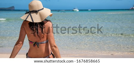 Beautiful woman wearing straw hat on the shoreline, back view, holiday concept. #1676858665