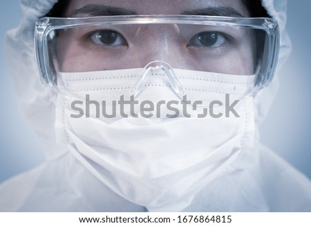 A doctor wearing personal protective equipment or ppe including mask, goggle, and suit to protect COVID-19 infection. coronavirus, medical, healthcare, quarantine concept Royalty-Free Stock Photo #1676864815