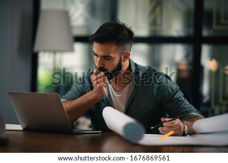 Businessman working on his laptop. Handsome young man working in office. #1676869561