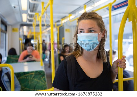 Young Woman Wearing a Face Mask Riding Public Transport Royalty-Free Stock Photo #1676875282