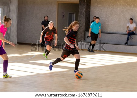 ODESSA, UKRAINE - March 13, 2020: Futsal Cup of Ukraine, futsal among students. During final match in futsal among student teams. Beautiful sports girls play mini football on parquet floor #1676879611