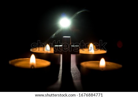 This is a picture of a candle and a cross in the dark.