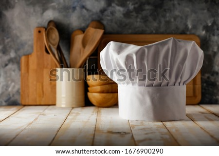 White cook hat on board and kitchen interior.  Royalty-Free Stock Photo #1676900290