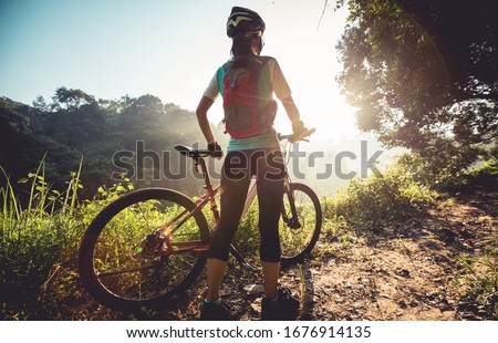 Young woman cyclist  enjoy the beautiful sunrise on summer forest trail Royalty-Free Stock Photo #1676914135