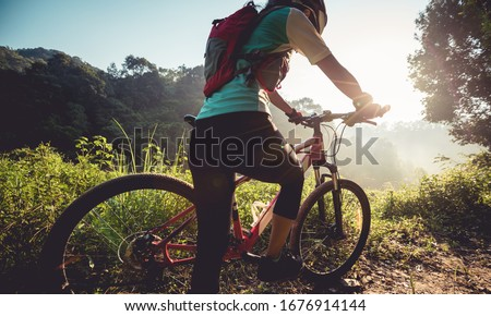 Young woman cyclist  enjoy the beautiful sunrise on summer forest trail #1676914144