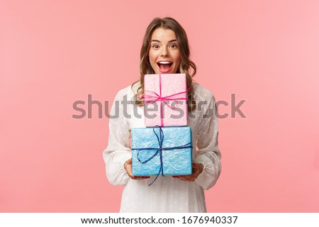 Holidays, celebration and women concept. Portrait of happy cheerful girl likes celebrating birthday and receive presents, holding two gift boxes and smiling camera, pink background Royalty-Free Stock Photo #1676940337