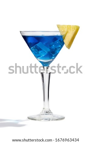 Blue Lagoon cocktail with ice cubes is contained in a martini glass with pineapple slice on the rim. The showy illustrative picture is made on the white background.