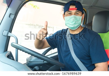 Photos of Asian truck drivers wearing masks to protect against dust and the spread of COVID 19 in front of the car. Safety ideas for a worker in the transportation business. And is a new normal life. #1676989639