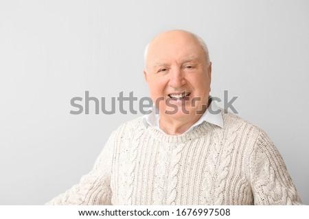 Portrait of elderly man on light background #1676997508
