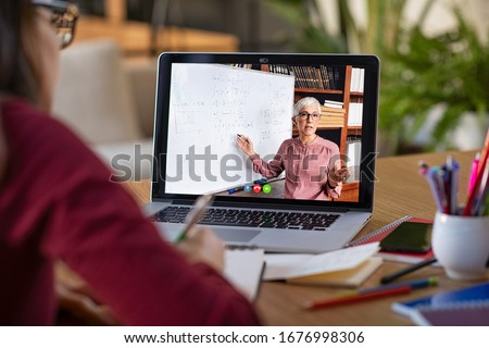 Young student watching lesson online and studying from home. Young woman taking notes while looking at computer screen following professor doing math on video call. Girl studying from home on pc. Royalty-Free Stock Photo #1676998306