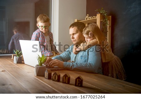 Work from home on laptop. Father and children boy and girl sitting on the table.  #1677025264