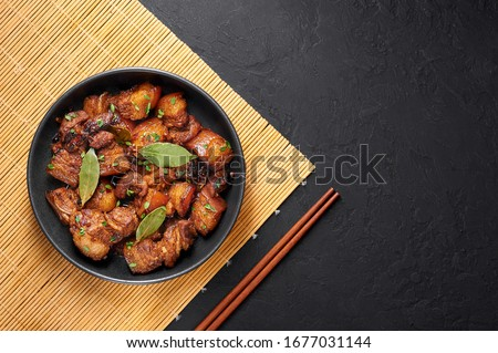 Adobo Pork in black bowl at dark slate background. Pork Adobo or Adobong Baboy is filipino cuisine dish with braised pork belly, bay leaves, soy sauce, vinegar and spices. Filipino food. Top view #1677031144