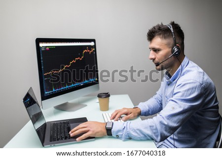 Side view of a happy male stock market broker looking at rising stock charts #1677040318