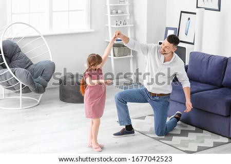 Father and his little daughter dancing at home #1677042523