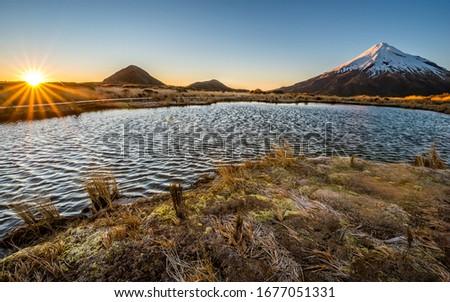 Mount Taranaki volcano mirror lake at sunrise. Shinning sun over mirror pools with Mount Taranaki covered by snow in spring. New Plymouth, Egmont National Park, North Island, New Zealand. #1677051331