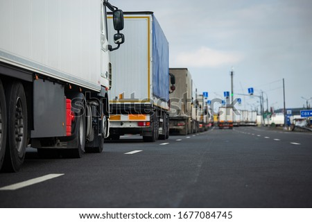 a long traffic jam of many trucks at the border , a long wait for customs checks between States due to the coronavirus epidemic, increased sanitary inspection of cargo transport Royalty-Free Stock Photo #1677084745