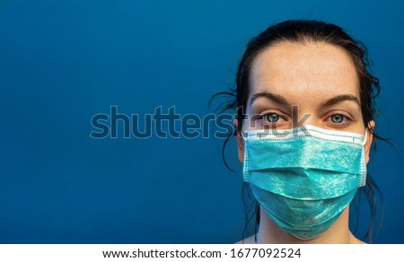 Tired female nurse, wearing a turquoise surgical mask, exhausted after a difficult day in the hospital helping  COVID-19, corona virus, patients. Standing against a blue wall with slogan, copy space. #1677092524