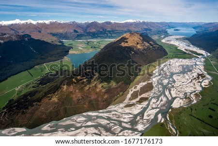 Aerial view of a huge riverbed and river mouth delta, glacial river system transporting water deposits from the Mount Aspiring glacier, Southern Alps, New Zealand. Mountain valley around Glenorchy. #1677176173