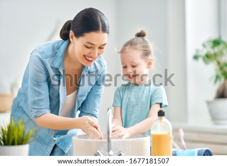A cute little girl and her mother are washing their hands. Protection against infections and viruses.                                #1677181507