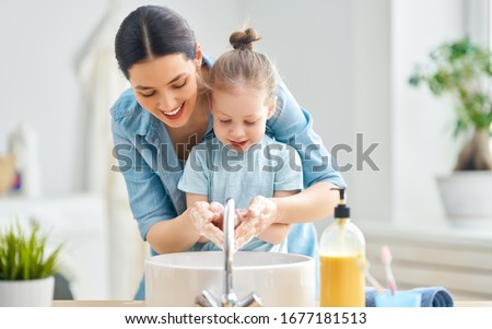 A cute little girl and her mother are washing their hands. Protection against infections and viruses.                                Royalty-Free Stock Photo #1677181513