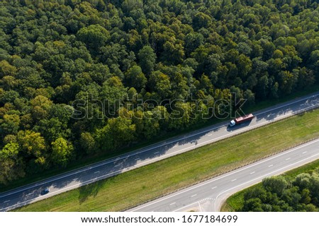 The truck is in a hurry to deliver the cargo, driving along a straight highway laid through the forest. Top view, shot on a drone.