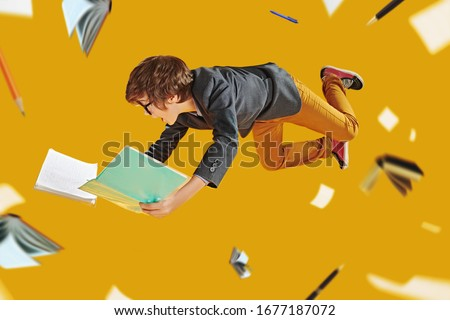 Educational concept. Smart boy teenager student preparing for lessons flies through the air surrounded by books and educational supplies. Yellow background with lights. Royalty-Free Stock Photo #1677187072