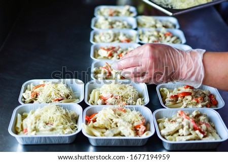 Food delivery. preparing food portions in containers. delivery service during quarantine covid-19. Chicken with vegetables and cheese. airline food. airline meals and snacks. takeaway selective focus #1677194959