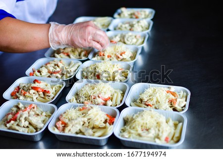 Food delivery. preparing food portions in containers. delivery service during quarantine covid-19. Chicken with vegetables and cheese. airline food. airline meals and snacks. takeaway selective focus #1677194974