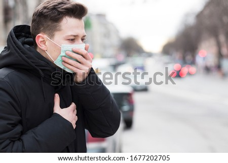 Side view of man in city coughing while wearing a medical mask  #1677202705