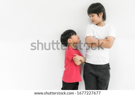 Little child boy and tall child boy standing arms crossed and looking face isolated on white background. Big and small kid concept at be friends. Back to school for concept. Royalty-Free Stock Photo #1677227677