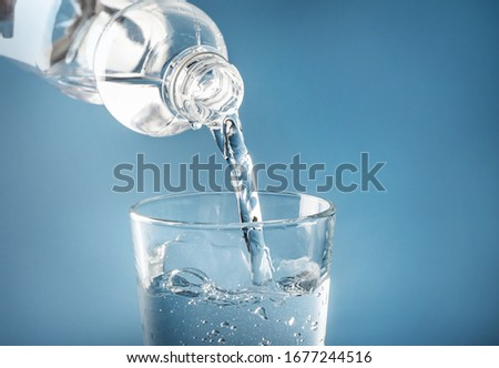Water pouring from plastic bottle in glass on blue background #1677244516